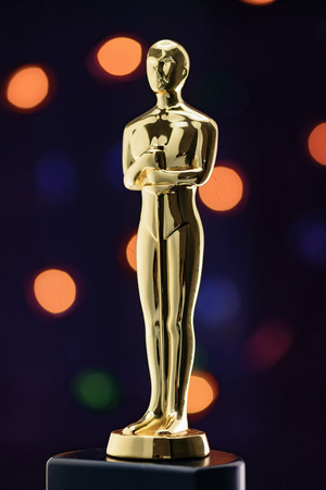 nominations: Full Shiney Golden Statuette on Defocused Lights Background