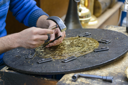 ancient blacksmith: Two Hands of Artist Engraving Brass Plate