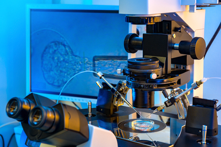 A Professional In Vitro Fertilisation Microscope with A Monitor in Background
