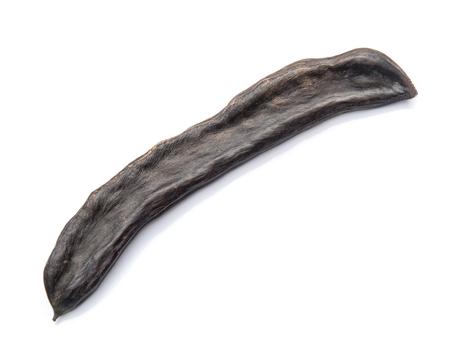 A Black Carob Pod on White Background Stock Photo