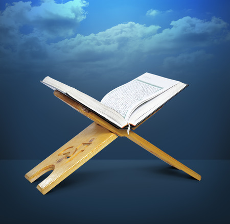 recite: Open Wooden Quran Stand Over Blue Background