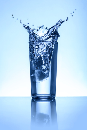 Natural Water Splash in A Glass Over Light Blue Background