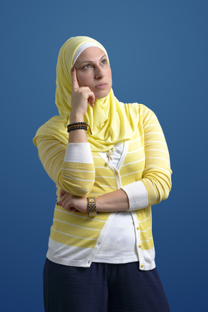 Beautiful Muslim Woman Thinking over Blue Background