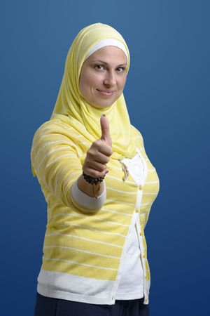 Thumbs Up Beautiful Muslim Woman over Blue Background