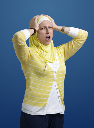 Stressed Muslim Woman over Blue Background