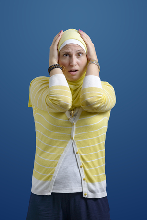 Sad Shocked Muslim Woman over Blue Background