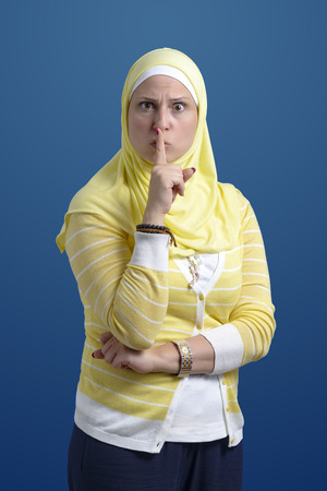 Beautiful Muslim Woman with Silence Gesture over Blue Background
