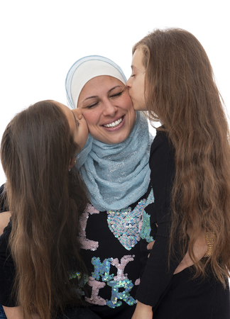 Young Beautiful Girls Kissing Their Happy Muslim Mother Celebrating Mothers Day Isolated on White Background