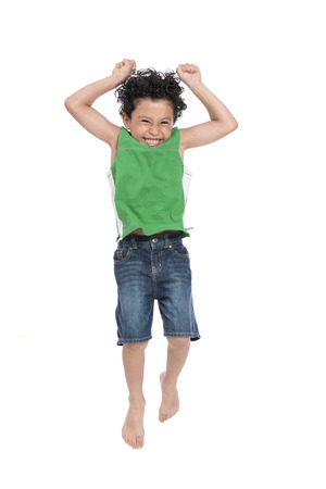 A Young Active Happy Boy Jumping in The Air Isolated on White Background