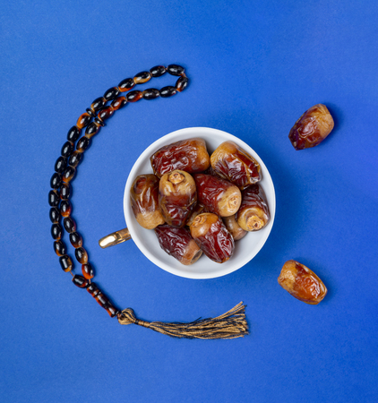Bowel of Ramadan Fresh Fruits, Dates and Rosary, on Blue