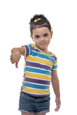 Pretty Little Female Child with Thumbs Down Expression, Dislike Emotion, Looking at The Camera, Studio Shot Isolated on White Background Фото со стока