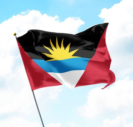 National Flag of Antigua and Barbuda Raised Up with Sky and Clouds in Background
