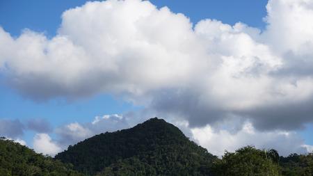White clouds over mountain peak Stock Photo