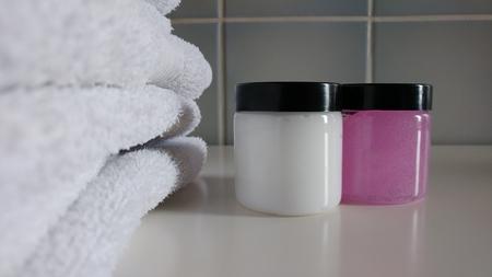 Weiße Handtücher und Kosmetikprodukte in gefliestem Bad