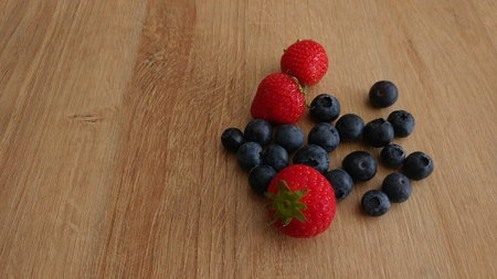 Blueberries and Strawberries on Wooden Background
