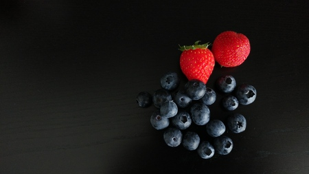 Blueberries and Strawberries on Black Background Imagens
