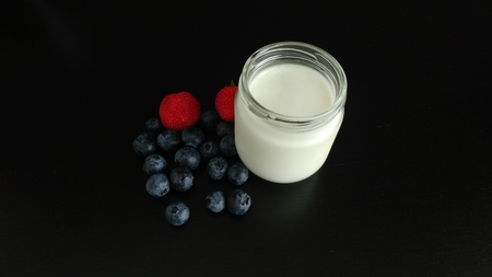 White Yogurt with Berries on a black tabletop Imagens