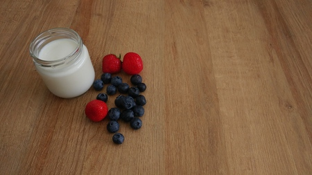 White Yogurt in Glass Jar with Berries on wooden tabletop