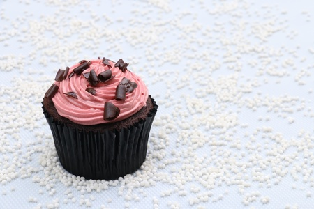 chocolate curls: Chocolate cupcake with strawberry buttercream frosting and chocolate curls topping