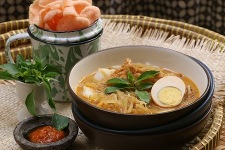 bean curd: A Javanese breakfast dish of rice cake egg bean curd jicama in spicy coconut milk broth. Served with crispy crackers and chili paste on side.