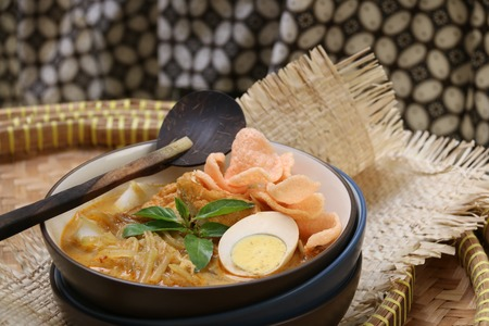 javanese: A Javanese breakfast dish of rice cake egg bean curd jicama in spicy coconut milk broth. Served with crispy crackers on top. Stock Photo