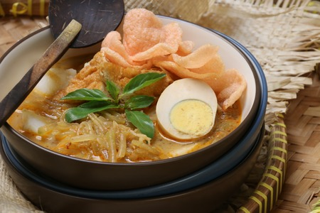 bean curd: A Javanese breakfast dish of rice cake with egg bean curd jicama in spicy coconut milk broth.  Served with crispy crackers on top. Stock Photo