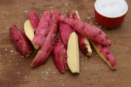 quartered: Japanese sweet potato cut lengthwise and seasoned, ready to be fried.