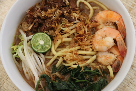 beansprouts: A close-up view of mie kangkung, noodle soup with water spinach kangkung as the main vegetable, with soy-braised beef, shrimps, beansprouts in beef broth. A dish from Betawi ethnic in Jakarta. Stock Photo
