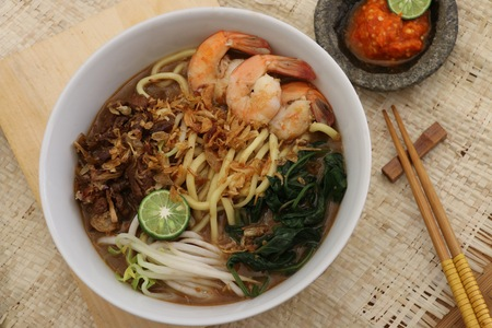 beansprouts: Mie kangkung, noodle soup with water spinach kangkung as the main vegetable, with soy-braised beef, shrimps, beansprouts in beef broth. A dish from Betawi ethnic in Jakarta. Served with chili paste and kaffir lime. Stock Photo