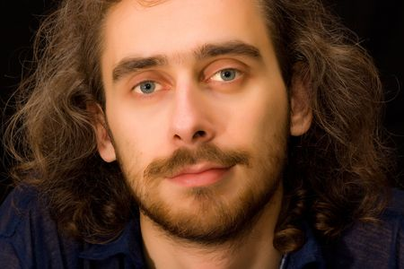 full face: Full face portrait of young adult brown-haired man, dark background, untidy curly hair