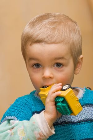 plactic: Cute small boy biting his plactic car toy, indoors, home background