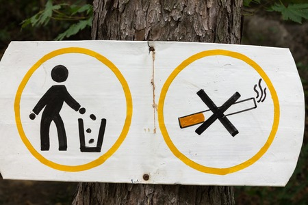 botar basura: se prohíbe fumar signo y tirar basura clavado en el árbol.