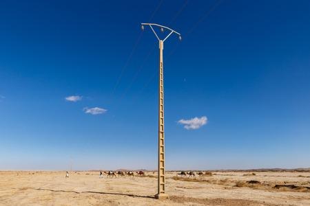 transmission line: caravan of camels goes on the background of a transmission line in the Sahara desert, Morocco