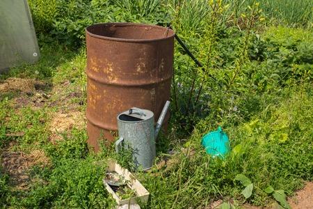 watering pot: watering pot and barrel of water in the garden.