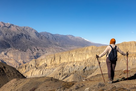 girl with a backpack and trekking poles looks at mountain pass Gyu La, Nepal