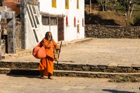 Bandipur, Nepal - NOVEMBER 24, 2016: Nepali aged pilgrim in orange robe in the temple of Bandipur in Nepal November 24 2016.