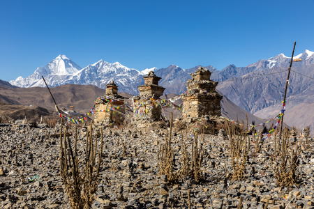 Buddhist chorten above Muktinath village, Dhaulagiri rising in the babkground. Stock Photo