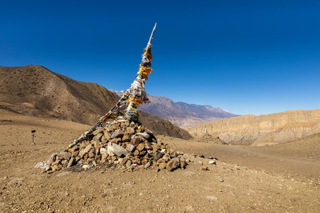 traditional tibetan pile of stones and colored flags Stock Photo