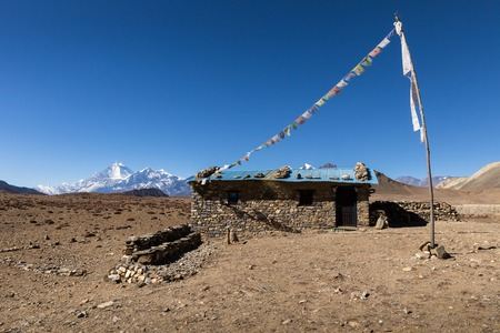 tibetan house: stone house with colored flags on a background of mountains, Himalayas, Nepal Stock Photo