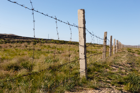 fence of barbed wire that separates the railway from the steppe, Mongolia Banco de Imagens