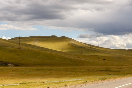 High-voltage power line runs through the hills in Mongolia, a beautiful Mongolian landscape Foto de archivo