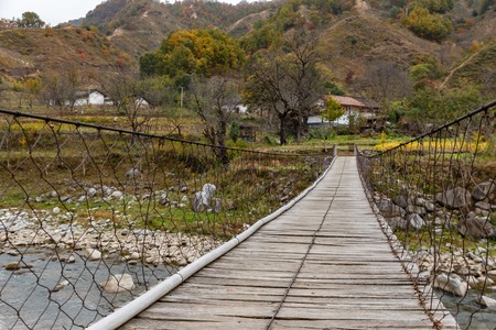wooden suspension bridge over a river in the mountains, China, Shaanxi Province, Stockfoto