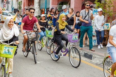 George Town, Penang, Malaysia - November 26, 2017: Happy people ride rented bicycles on a city street.