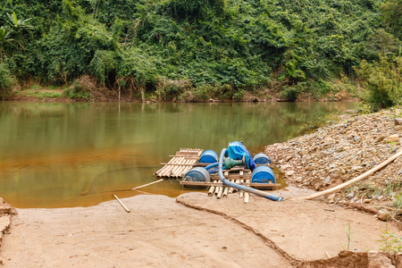 water pump on the river bank on a bamboo raft, Laos. Reklamní fotografie