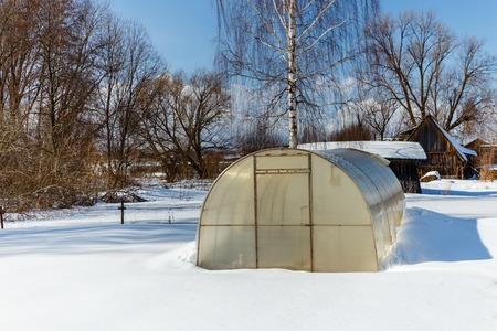 Small greenhouse with a metal frame covered with polycarbonate in a winter garden. greenhouse in winter Stock Photo