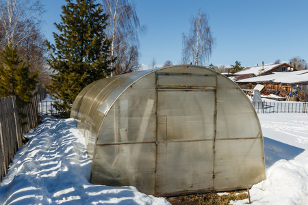 Small greenhouse with a metal frame covered with polycarbonate. greenhouse in winter