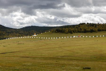 Buddhist monastery in Mongolian steppe, Stupas along the wall of a Mongolian monastery, Bornuur, Mongolia. Stock Photo