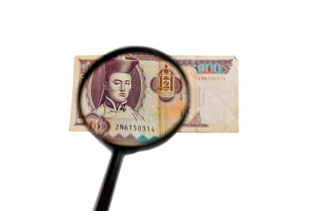 one hundred Mongolian tugriks bank note and magnifying glass isolated on white background