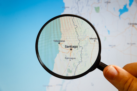 Santiago, Chile. Political map. The city on the monitor screen through a magnifying glass in hand. Stockfoto