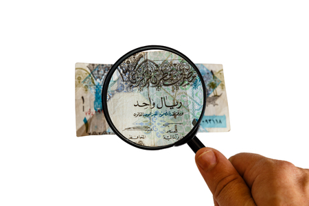 one Qatar Riyal and magnifying glass in hand isolated on white background, obverse front side